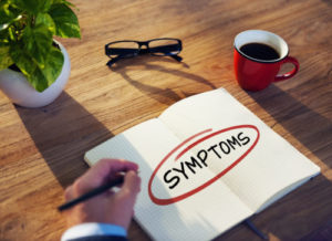 "Businessman Writing the Word ""Symptoms"""